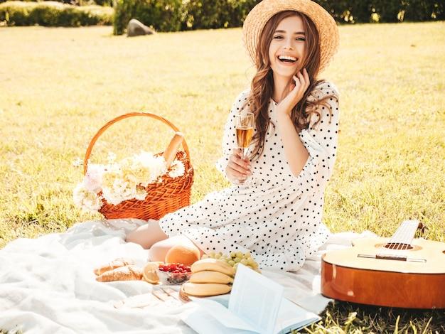 Молодая красивая битник женщина в модном летнем сарафане и шляпе. беззаботная женщина делает пикник на улице.