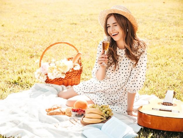 トレンディな夏のサンドレスと帽子の若い美しい流行に敏感な女性。外でピクニックをするのんきな女性。