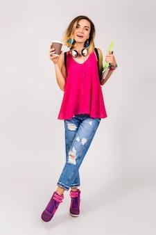 Giovane bella donna hipster, scarpe rosa e top holding libri e prendere il caffè