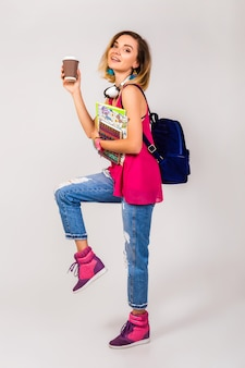 Young beautiful hipster woman, pink shoes and top holding books and taking coffee