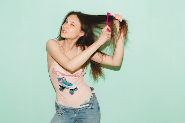 Young beautiful hipster woman posing against blue wall, combing long hair