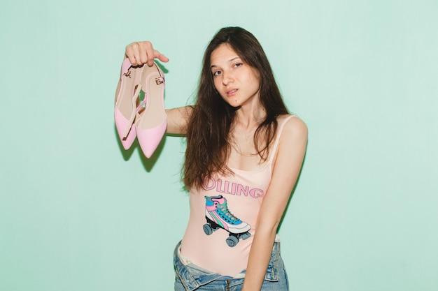 若い美しい流行に敏感な女性が青い壁にポーズ、手でトレンディな靴のペアを保持