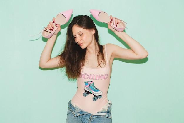 Giovane bella donna hipster in posa contro il muro blu, tenendo in mano un paio di scarpe alla moda