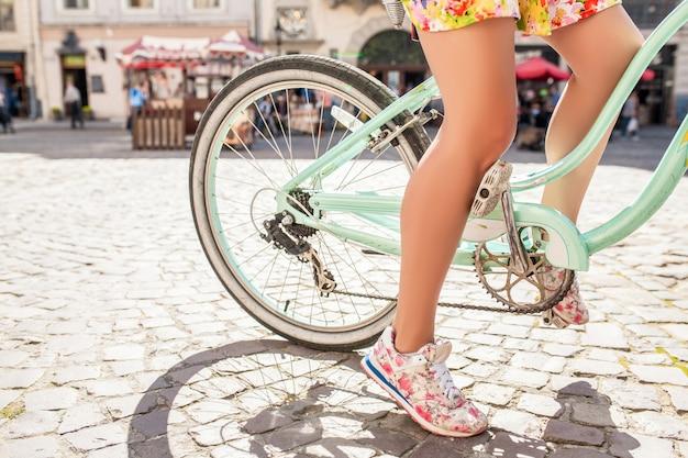 Donna giovane bella hipster cavalcando bicicletta sulla vecchia strada della città