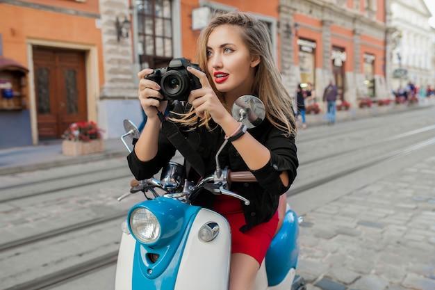 Donna giovane bella hipster in sella con la macchina fotografica sulla strada della città di moto