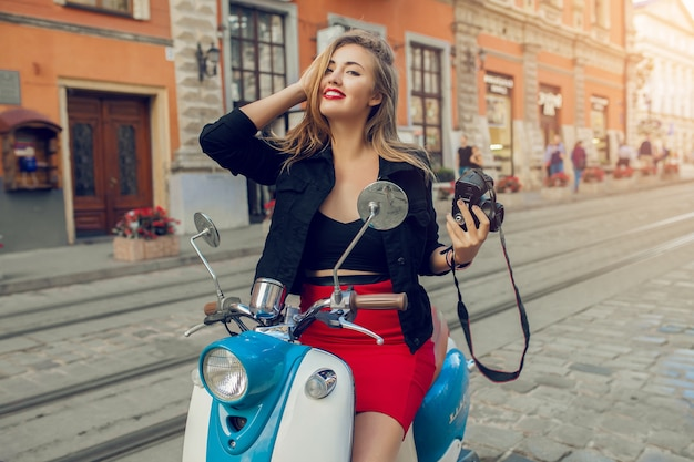 Young beautiful hipster woman riding with photo camera on motorbike city street