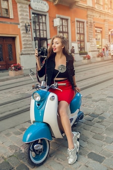 バイクの街の通りに写真カメラで乗る若い美しい流行に敏感な女性