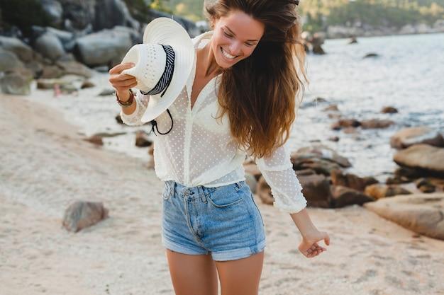 Giovane bella donna hipster in vacanza estiva in asia, rilassante sulla spiaggia tropicale, stile boho casual, paesaggio marino, corpo abbronzato sottile, viaggio da solo, capelli lunghi