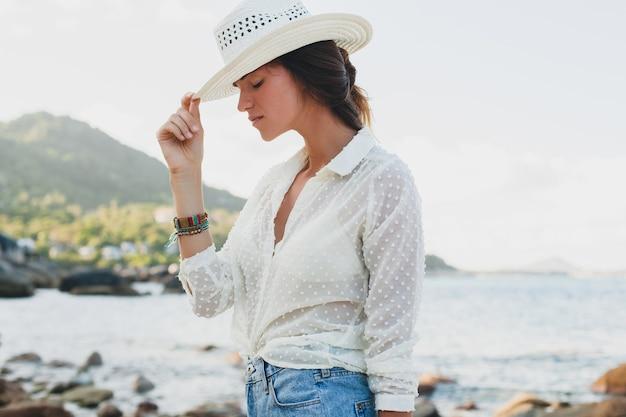 Giovane bella donna hipster in vacanza estiva in asia, rilassante sulla spiaggia tropicale, stile boho casual, paesaggio marino, corpo sottile abbronzato, viaggio da solo
