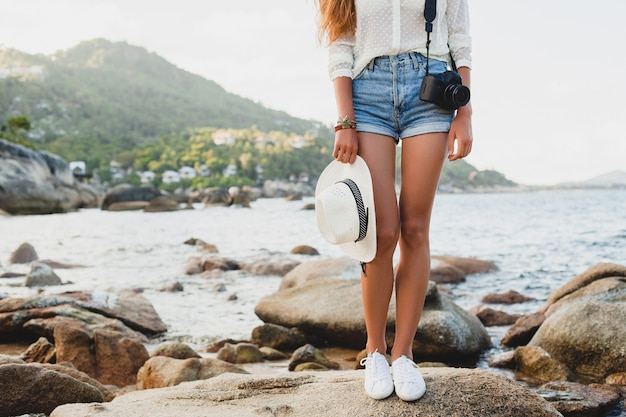 Giovane bella donna hipster in vacanza estiva, asia, rilassante sulla spiaggia tropicale, fotocamera digitale, stile boho casual, paesaggio marino, corpo abbronzato sottile, viaggio da solo, accessori di dettaglio da vicino