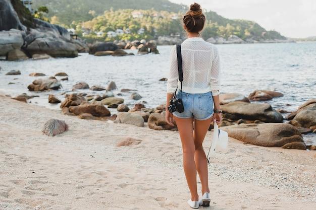 Giovane bella donna hipster in vacanza estiva in asia, rilassante sulla spiaggia tropicale, fotocamera digitale, stile boho casual, paesaggio marino, corpo abbronzato sottile, viaggio da solo, libertà