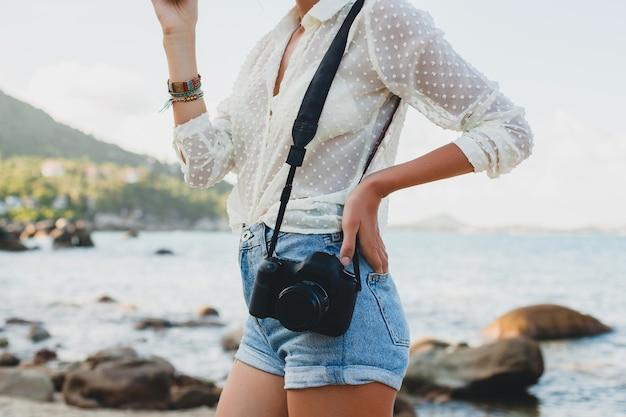 Giovane bella donna hipster in vacanza estiva in asia, rilassante sulla spiaggia tropicale, fotocamera digitale, stile boho casual, paesaggio marino, corpo abbronzato sottile, viaggio da solo