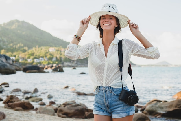 Young beautiful hipster woman on summer vacation in asia, relaxing on tropical beach, digital photo camera, casual boho style, sea landscape , slim tanned body, travel alone
