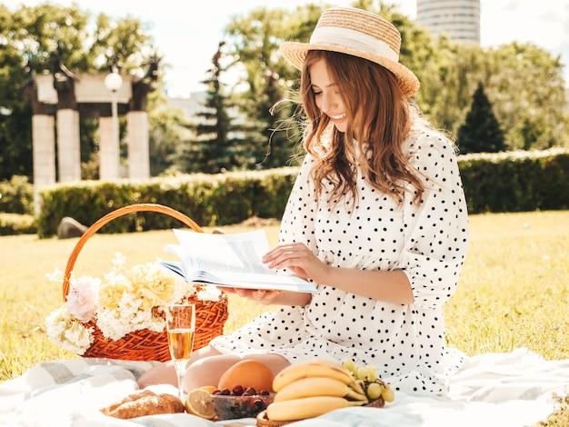 Giovane bella donna hipster in abito estivo alla moda e cappello. donna spensierata che fa picnic all'esterno.