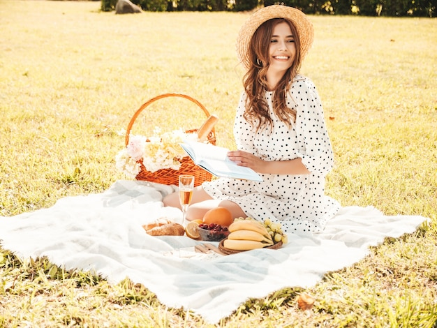 Young beautiful hipster woman in trendy summer dress and hat. carefree woman making picnic outside.