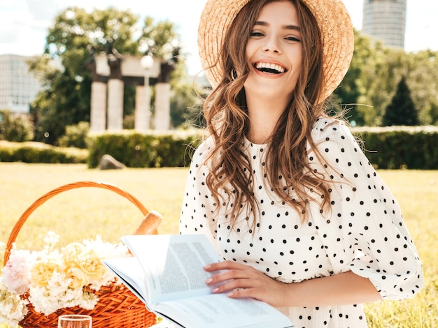 Young beautiful hipster woman in trendy summer jeans, pink t-shirt and hat. carefree woman making picnic outside.