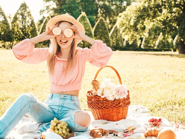Giovane bella donna hipster in jeans estivi alla moda, maglietta rosa e cappello. donna che fa picnic all'esterno.