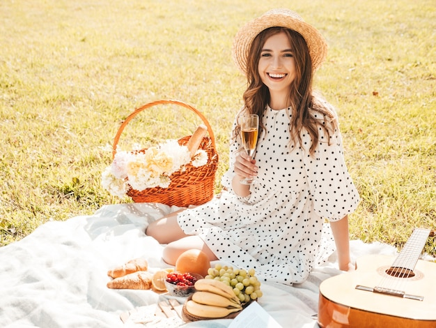 Young beautiful hipster woman in trendy summer sundress and hat. carefree woman making picnic outside.