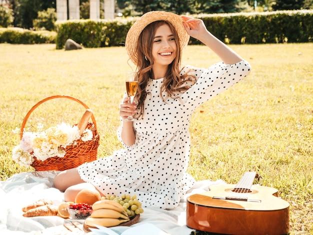 Giovane bella donna hipster in prendisole e cappello estivi alla moda. donna spensierata che fa picnic all'esterno.