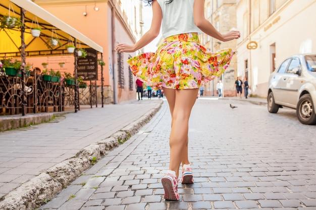 Donna giovane bella hipster che cammina sulla vecchia strada della città