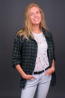 灰色の壁にブロンドの髪を持つ若い美しい流行に敏感な女性