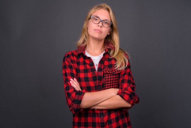 灰色の壁に眼鏡をかけているブロンドの髪を持つ若い美しい流行に敏感な女性