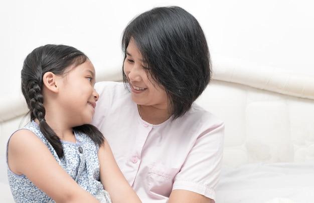 젊은 아름다운 히스패닉 어머니와 딸이 서로보고 웃 고, 사랑과 재미 개념