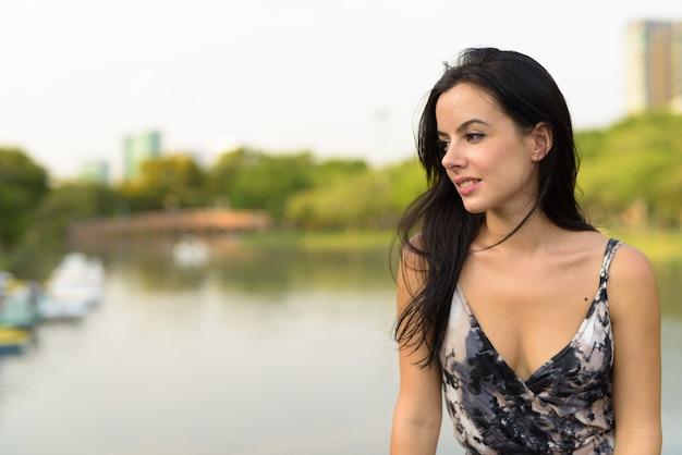 Young beautiful hispanic woman relaxing in the park