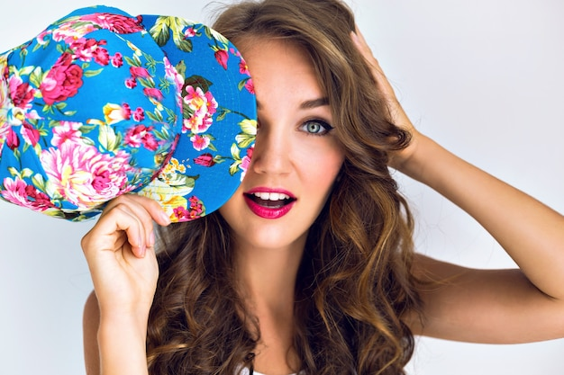 Молодая красивая горячая сексуальная женщина закрыла глаза цветочной крышкой. яркий макияж с красными губами и длинными вьющимися волосами. удивленные эмоции.