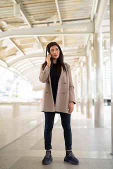 市内の電話で話している若い美しいインドの実業家