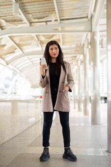 市内で電話を使用しながら考えて若い美しいインドの実業家