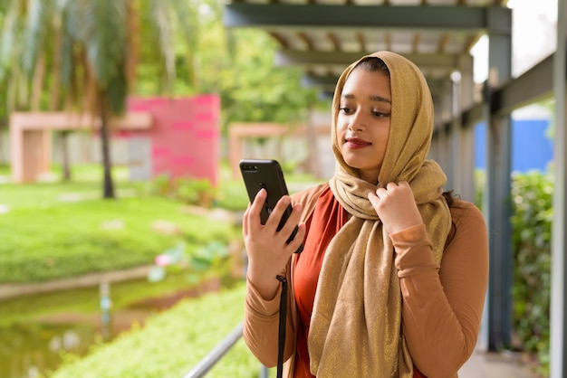 Young beautiful indian muslim woman using phone at the park