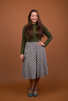 茶色の壁に対して若い美しいインドの女性