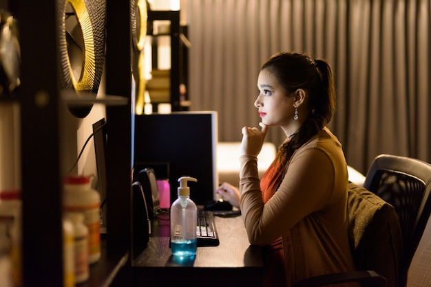 Young beautiful indian woman thinking while working from home late at night