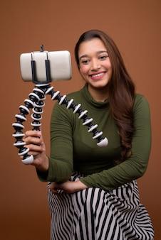 Молодая красивая индийская женщина ведет видеоблог с мобильного телефона против