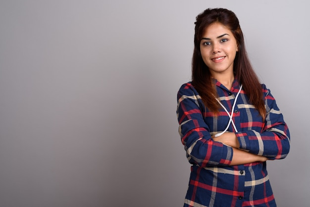 Young beautiful indian woman wearing checked shirt against gray