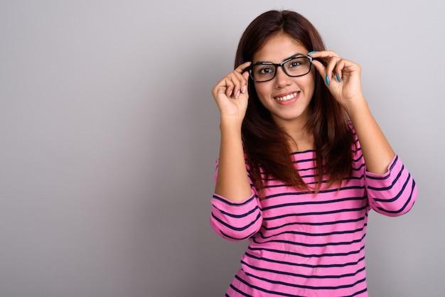 灰色の壁に眼鏡をかけている若い美しいインドの女性