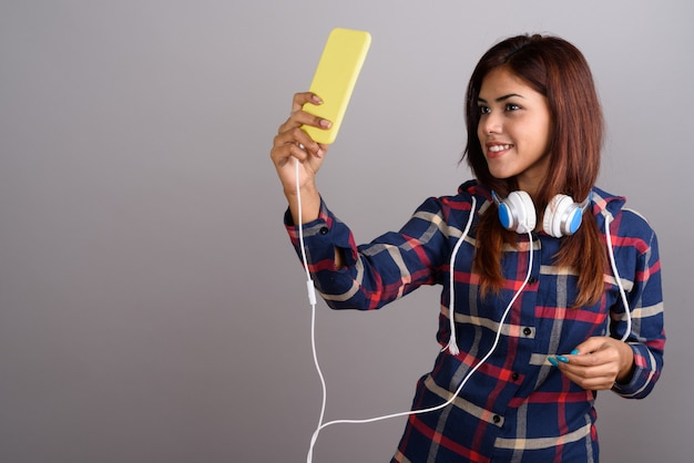 Young beautiful indian woman wearing headphones and using mobile