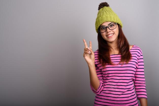 Молодая красивая индийская женщина в вязаной шапке на серой стене