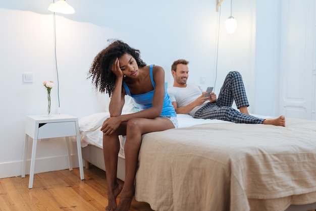 Young beautiful interracial couple in bed stressed with infidelity problems