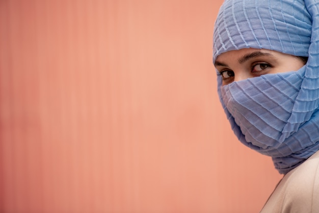 Young beautiful islamic female with her face hidden behind blue hijab looking at you in isolation