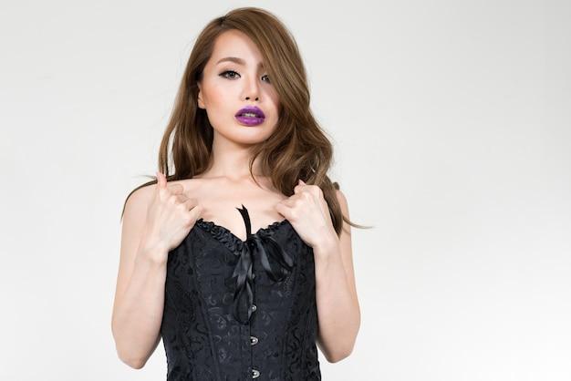 Молодая красивая японская женщина в корсете как сексуальная концепция у белой стены