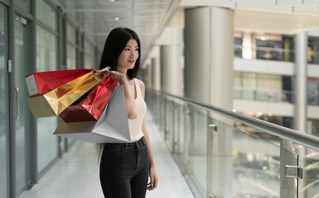 Young beautiful korean woman in the mall makes purchases. stands and holds packages in his hands. baner, place for text, copy space,