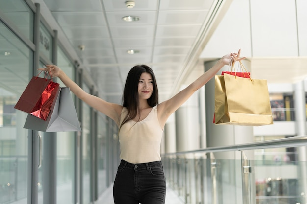 Young beautiful korean woman in a shopping mall with packages in hands. happy shopping days.
