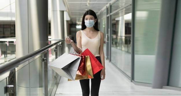 Young beautiful korean woman stands in a shopping mall. holds shopping bags in his hands. protective medical mask worn on the face.place for text