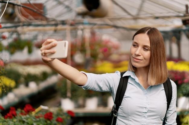 Молодая красивая дама делает селфи на фоне цветов в теплице
