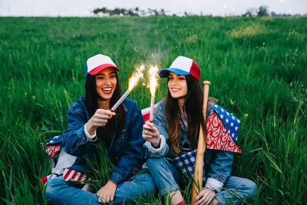 Giovani belle signore che celebrano il 4 luglio in campo