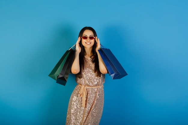 Young beautiful lady in beige dress with red glasses holding many shopping bags after successful shopping.