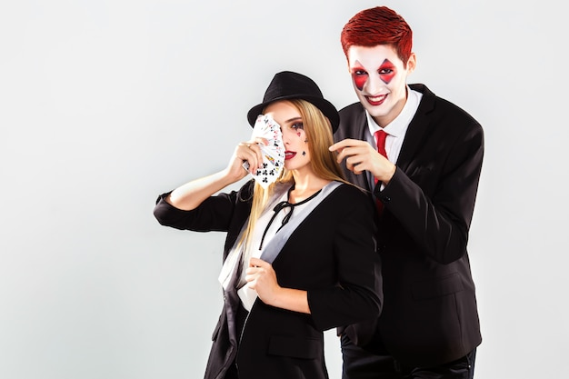 A young beautiful lady croupier and boy with an artistic make up joker . gamble and casino concept. studio shot. white background .