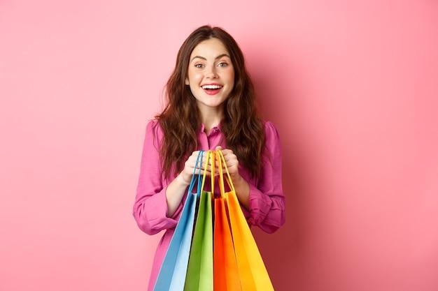 買い物に行く、バッグを持って、興奮して笑って、割引で購入し、ピンクの壁に立っている若い美しい女性。